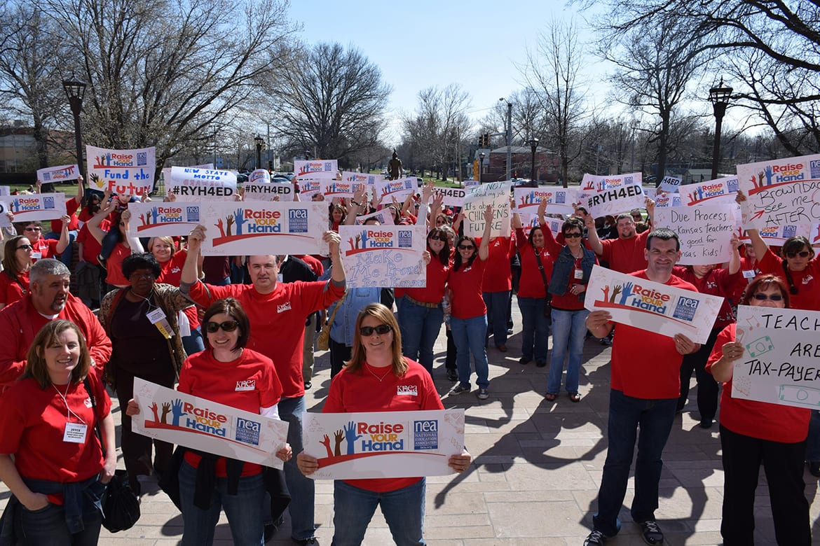 Photo of group of people outside in red shirts holding signs.