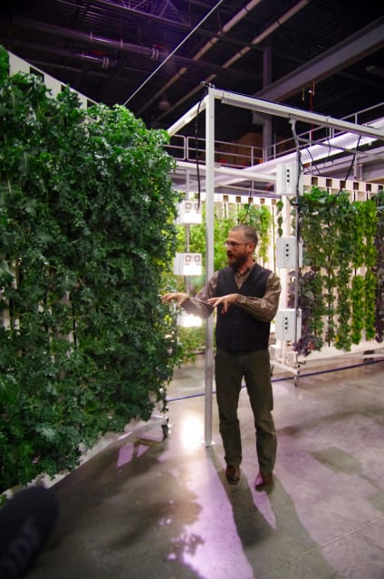 Bright Agrotech CEO Nate Storey demonstrates how indoor, vertical farming works in the company's Laramie warehouse. (Photo: Stephanie Joyce | Harvest Public Media)