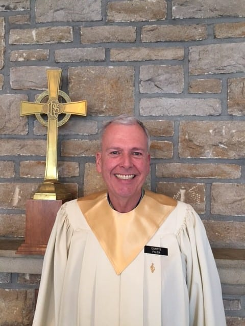 A man in front of a cross
