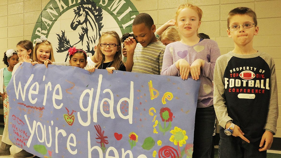 Franklin Smith kids welcoming visitors with a banner