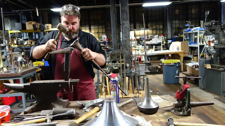 A man hammering a metal