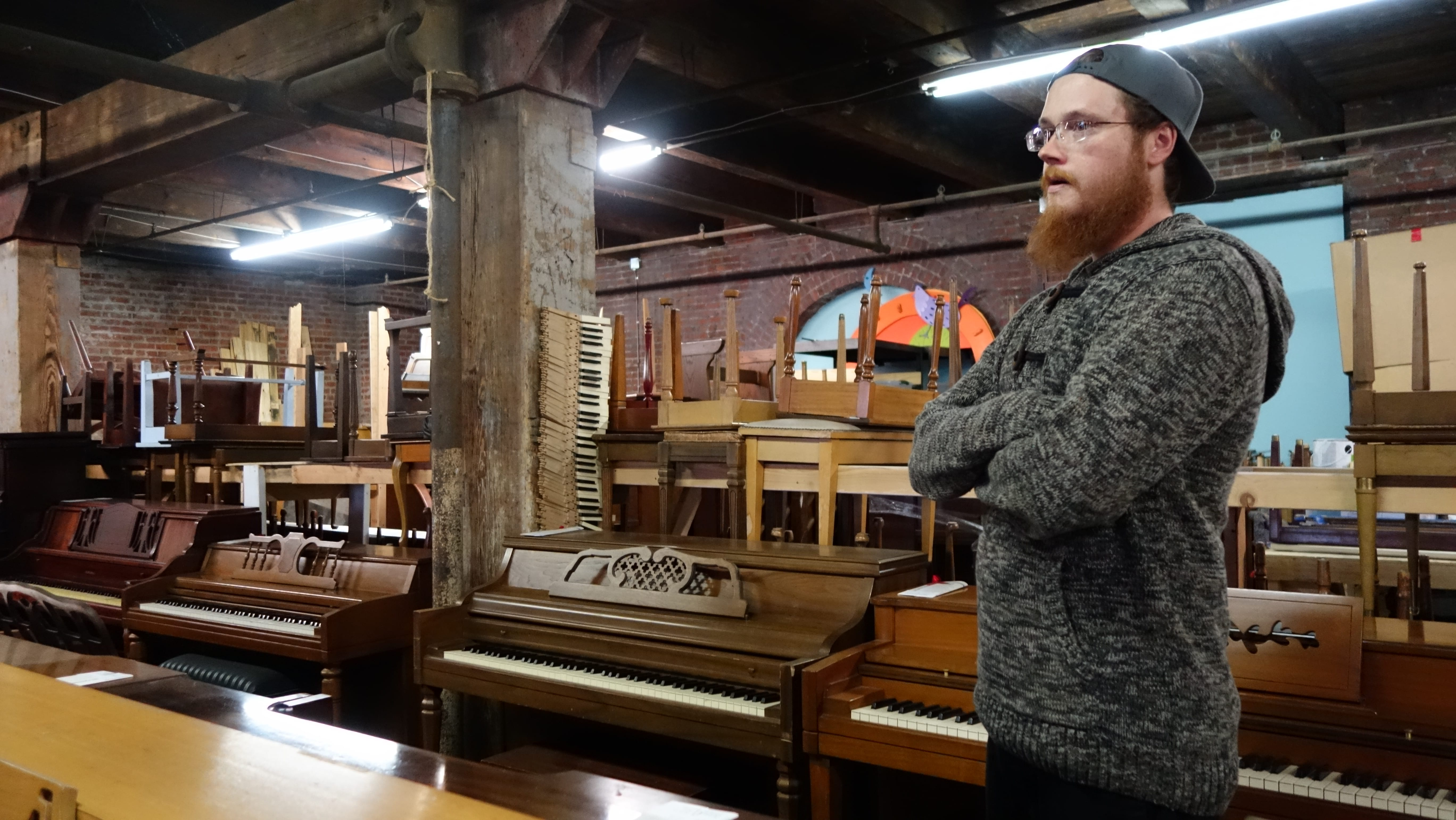 A man standing near pianos.