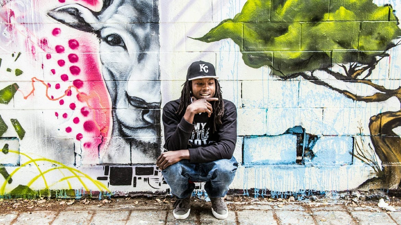 A rapper in front of graffiti