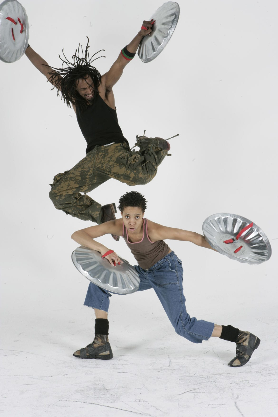 Two people dancing with trashcan lids.