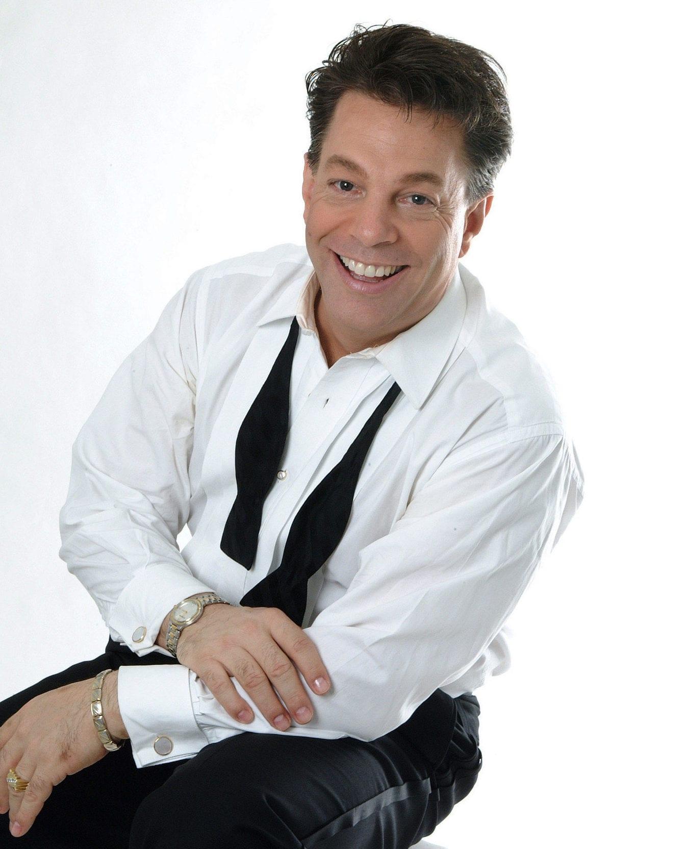 A man posing in a tuxedo.