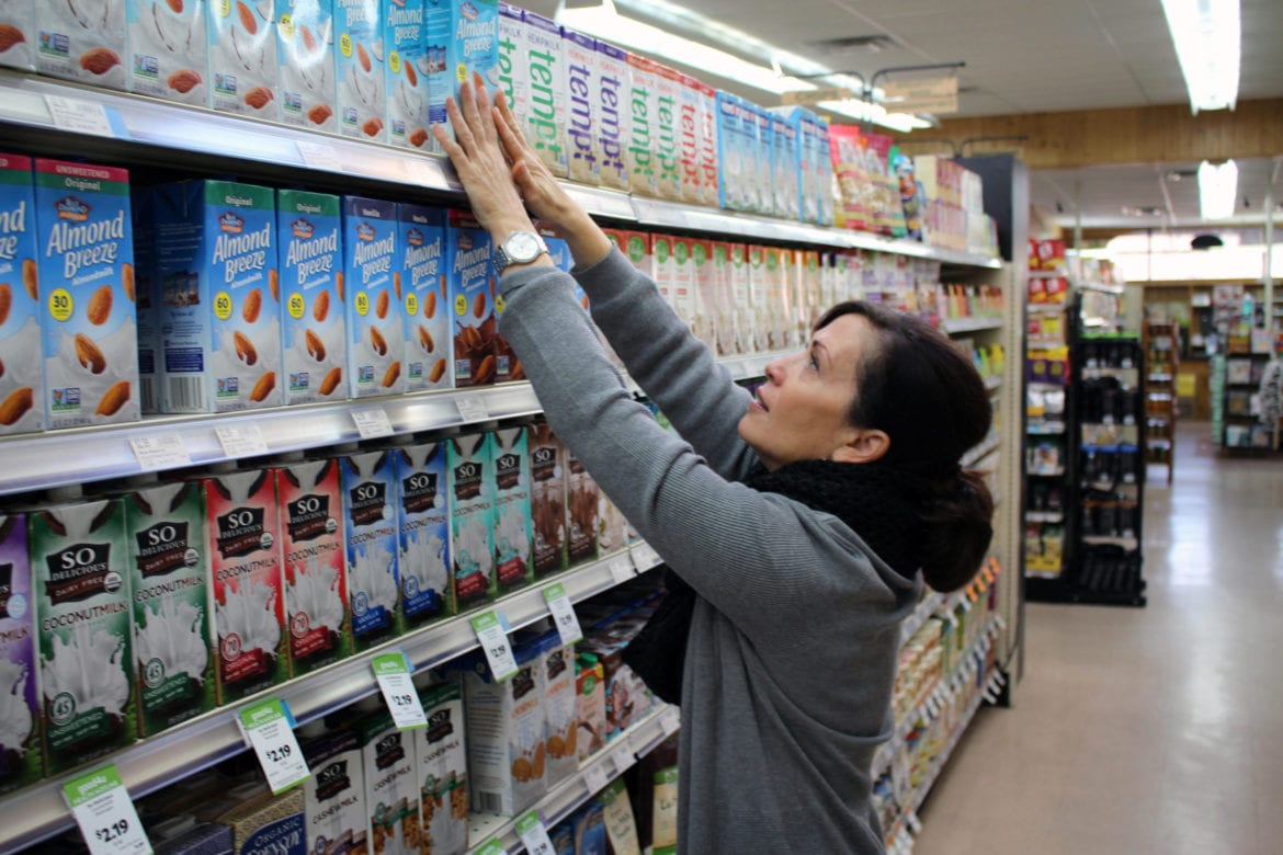 A woman reaching for non-dairy milk.