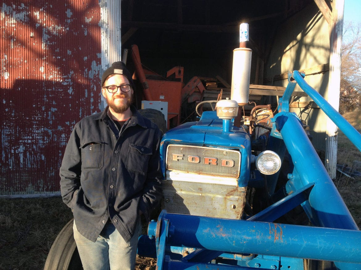 A man by a blue farm machine.