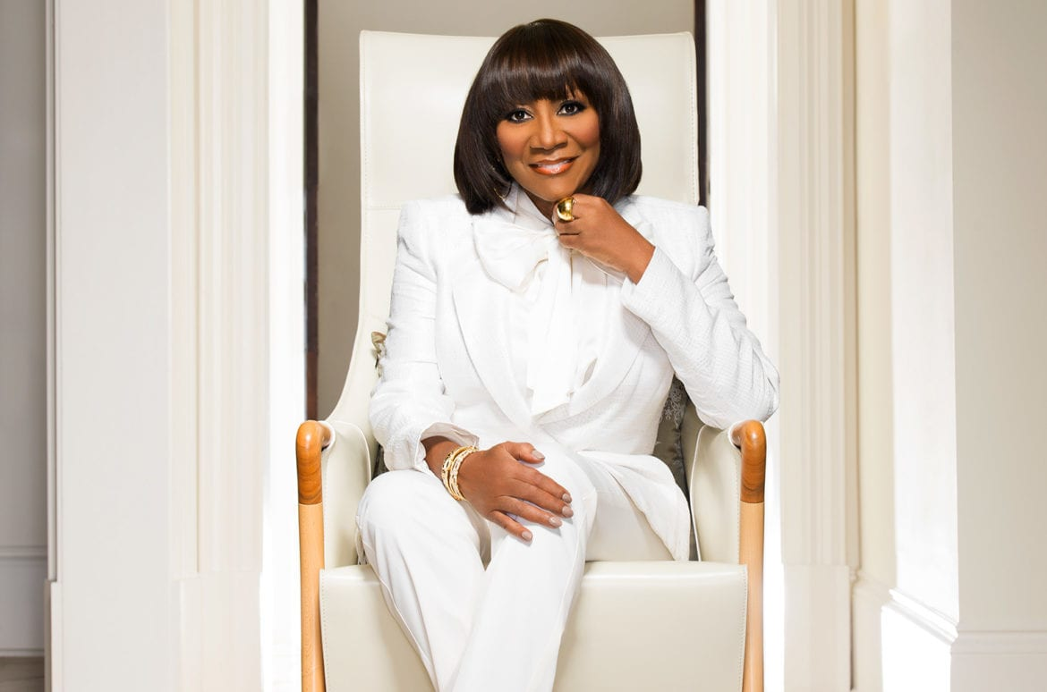 A woman in a white suit sitting.