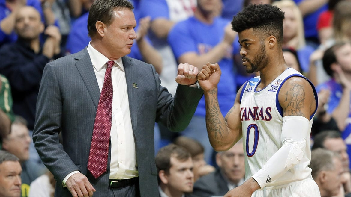 A basketball coach and player bump fists