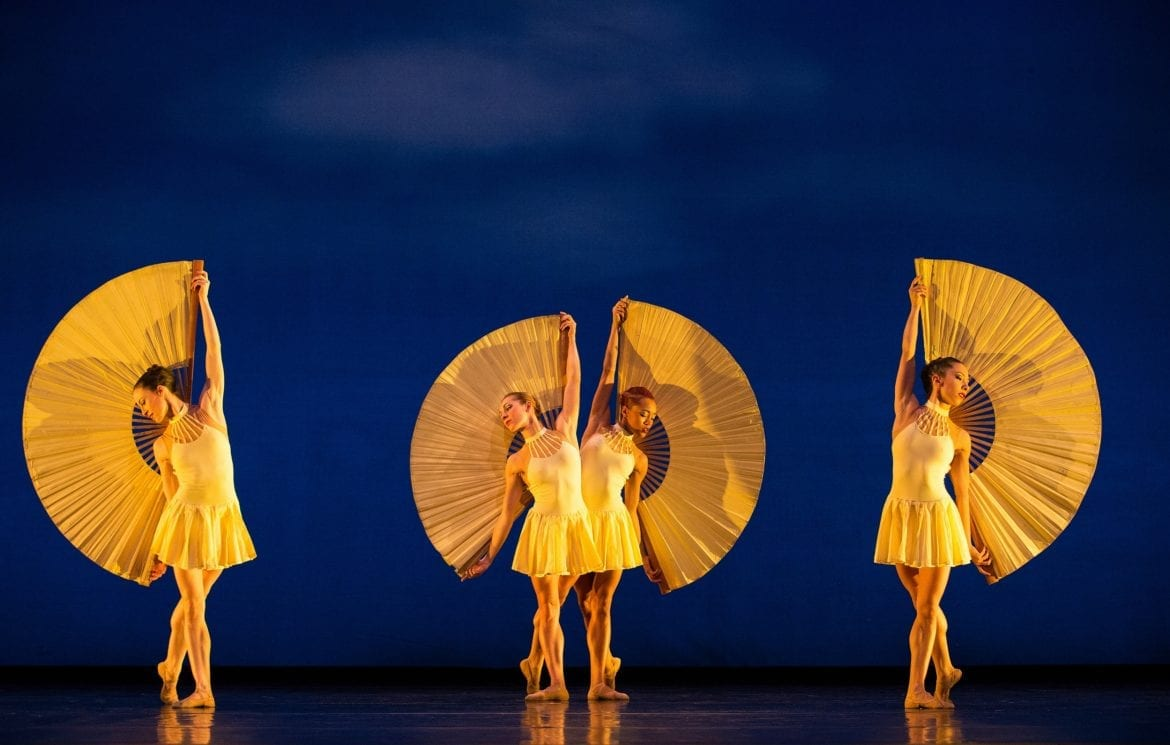 Four women in yellow costume posing against a blue backdrop.