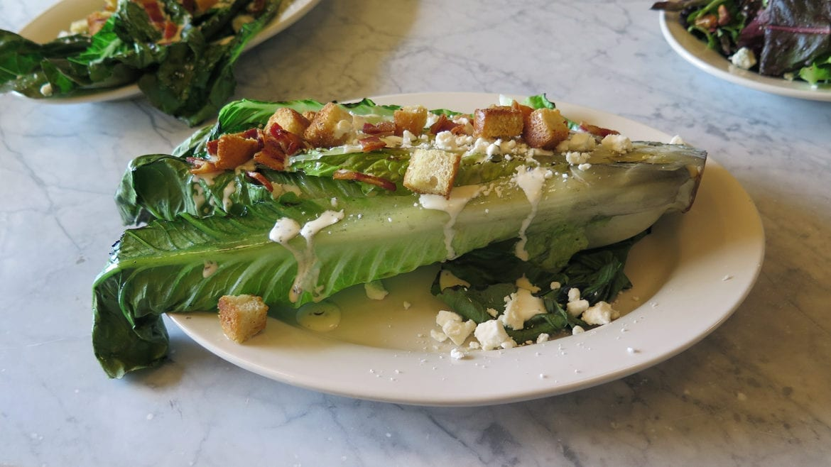 grilled romaine salad with bacon and feta cheese.