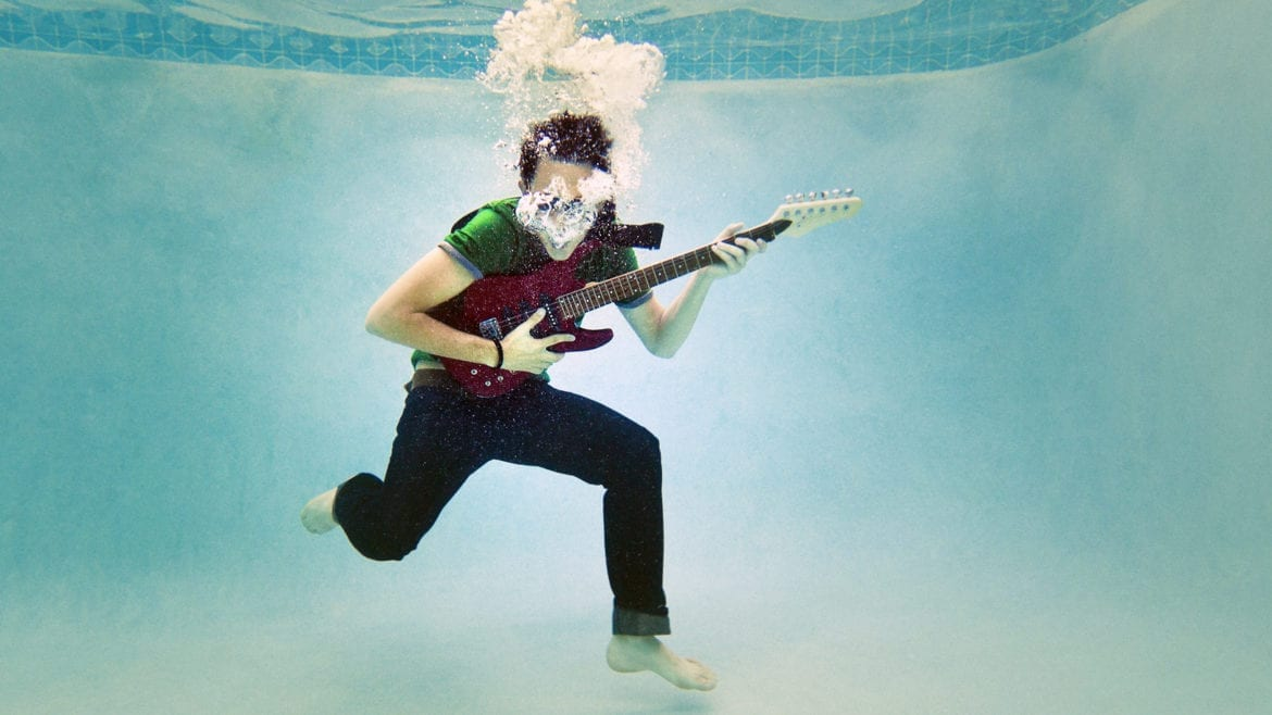 a teenager playing a guitar underwater
