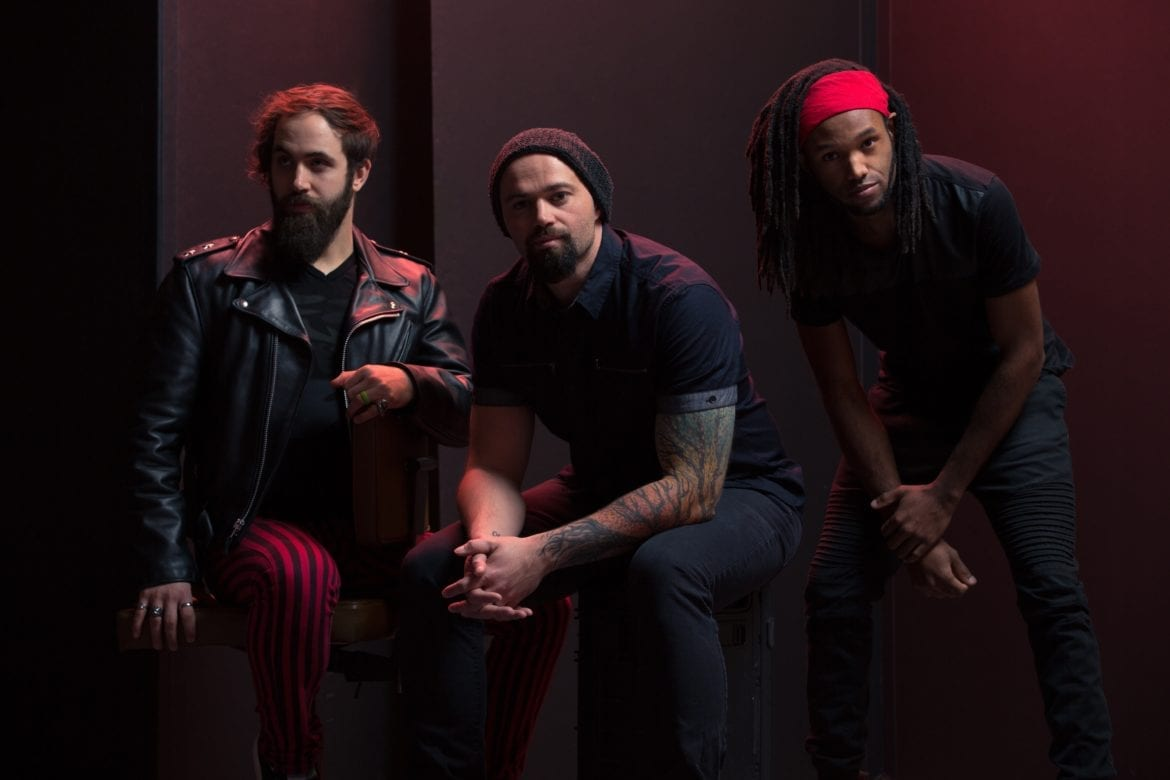 Three men in a band sit in a dark room.