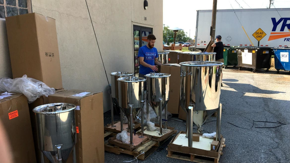 Brian Bixby and Brian Freymuller (back) unpack the fermenters